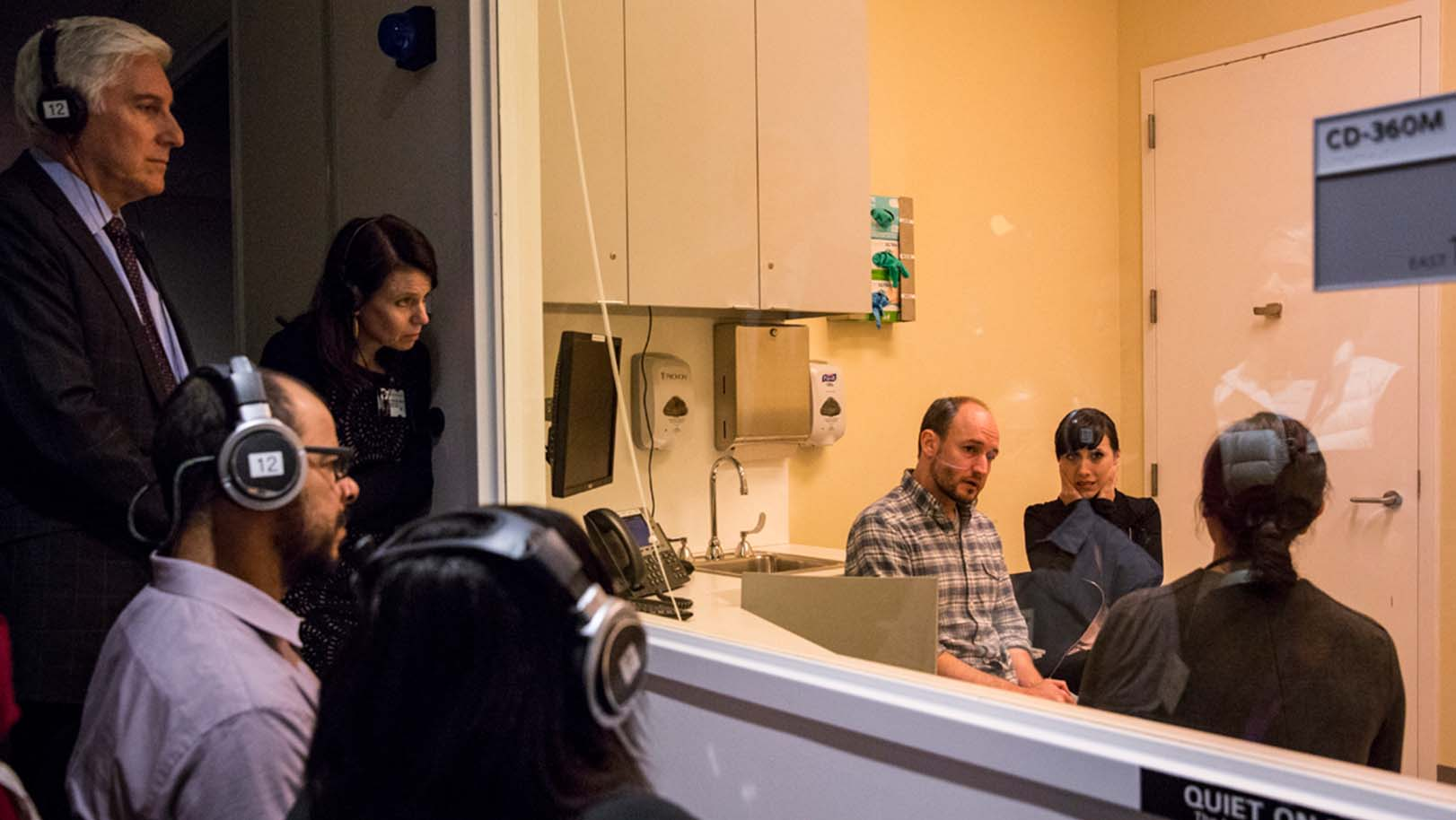 Training participants observe Sala Patient and Family Faculty members, clinical experts, and professional actors portraying patients and families during a scenario-based immersive simulation.