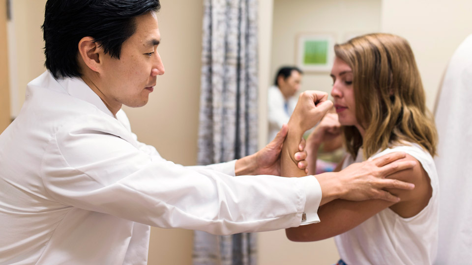 Dr. Andrew Chi Performs Strength Test on Patient