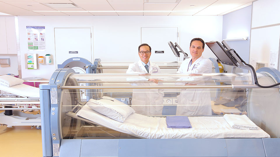 Dr. Frank Ross and Dr. Ernest Chiu with Hyperbaric Oxygen Therapy Chamber