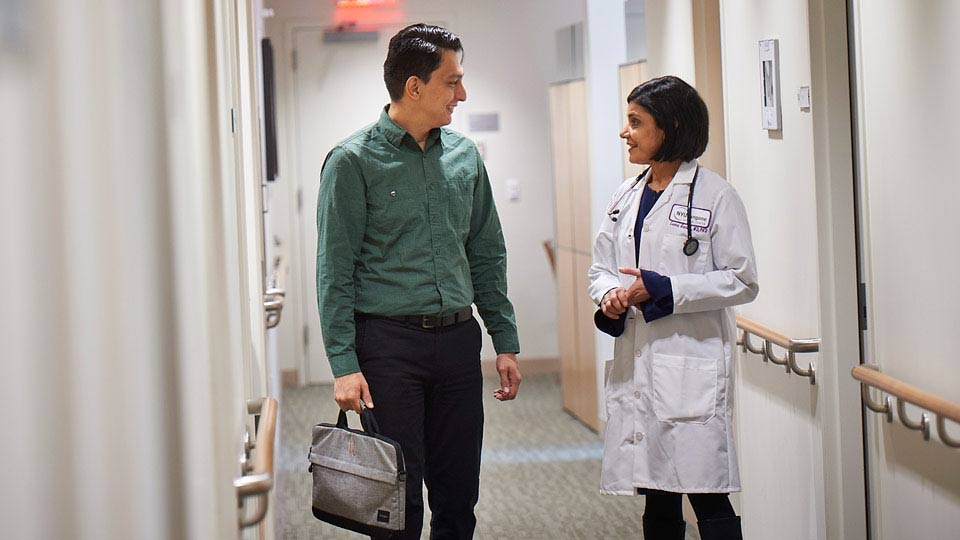 Dr. Leena Gandhi and Patient Chat in Hallway