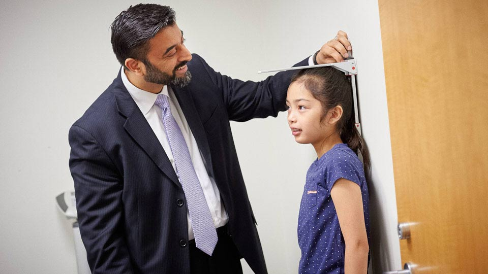 Dr. Rahil Jummani measures a patient's height at the Child Study Center