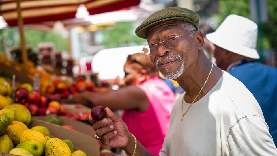 Man Holding Fruit at Fruit Stand