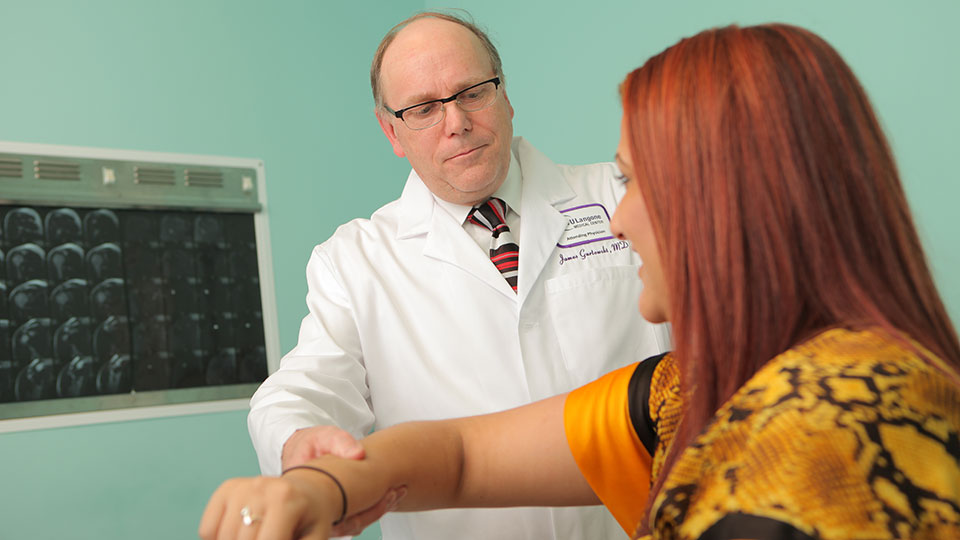 Orthopaedic Surgeon Dr. James Gurtowski Examines Patient