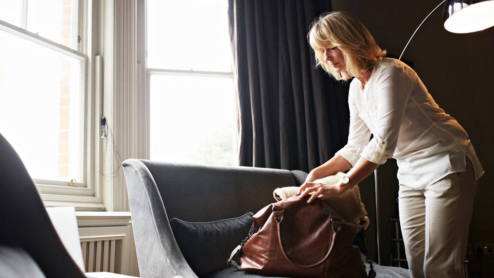 Woman Packing Handbag with Belongings