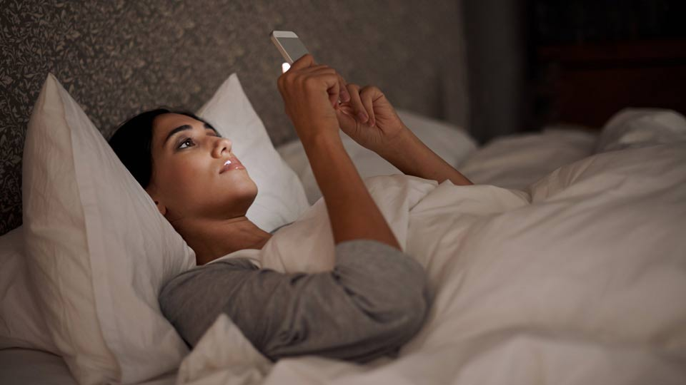 Woman Reading Her Phone in Bed