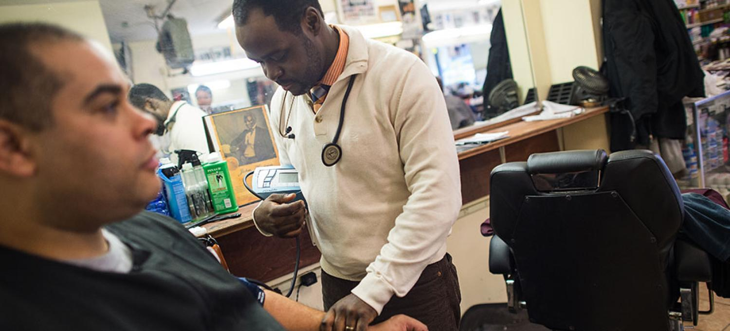 Dr. Joseph Ravenell Takes a Blood Pressure Reading From Man in Barbershop Chair