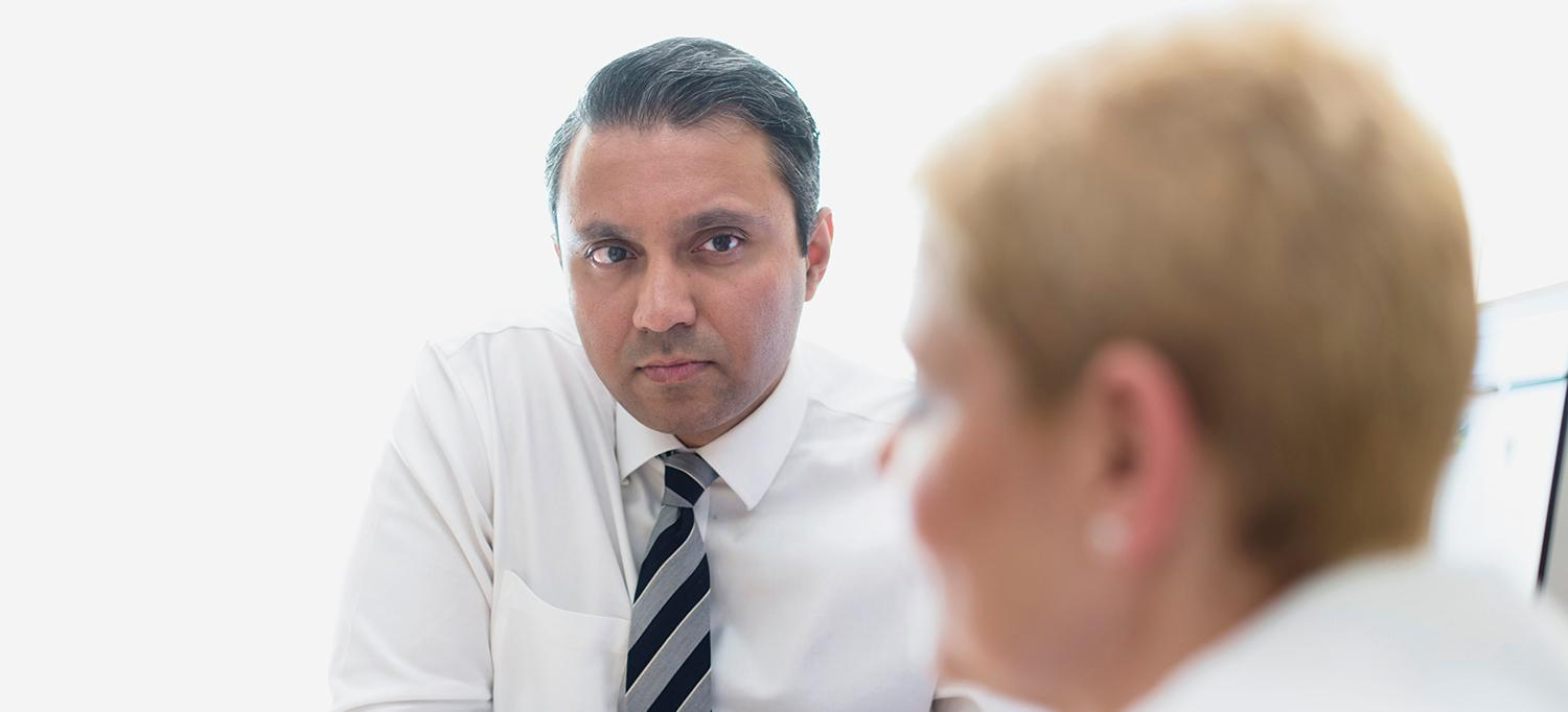 Arjun V. Balar, MD, Speaks with a Colleague in an Office