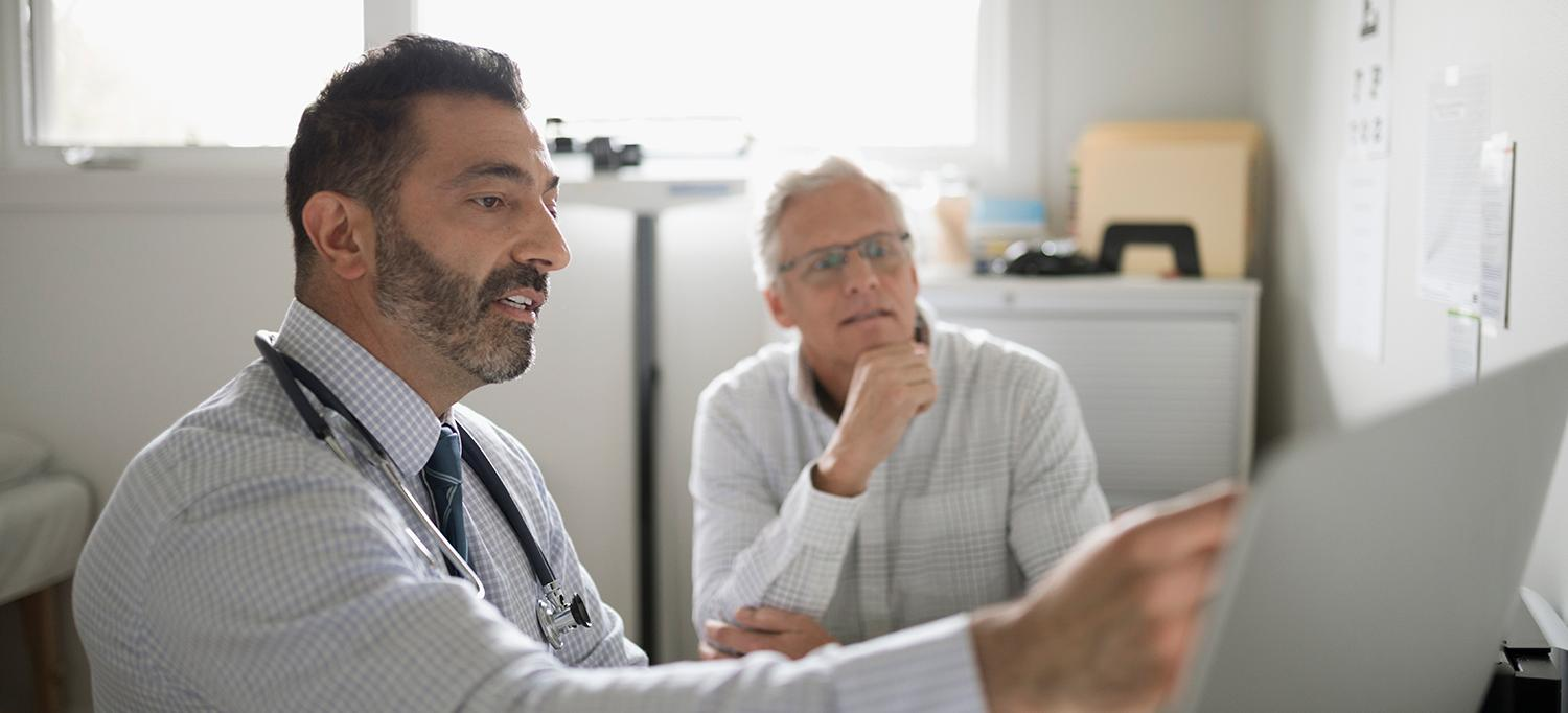 Doctor Reviews Chart with Patient