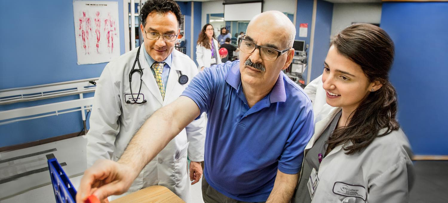 Dr. Jeffrey S. Fine and Colleague Help Patient with Rehabilitation Exercise