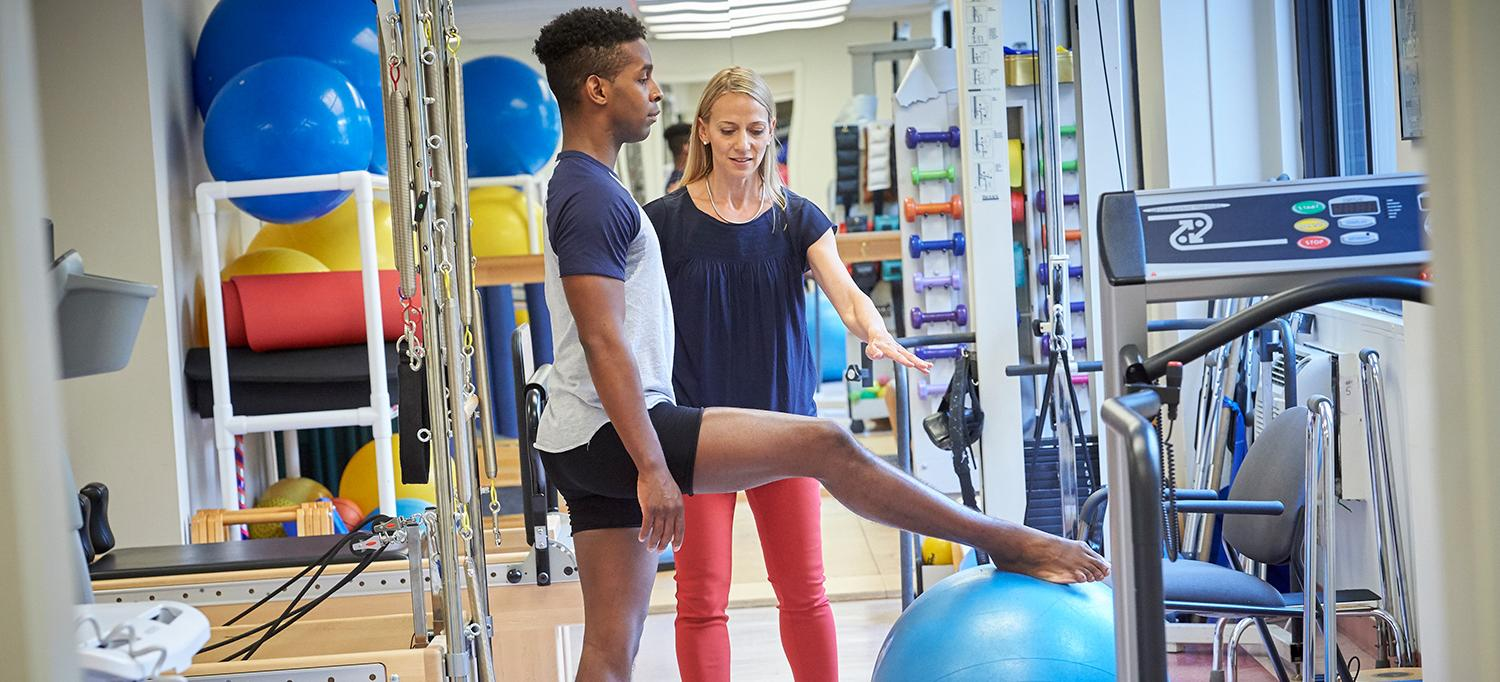 Physical Therapist Emily Sandow Works with Patient in Gym