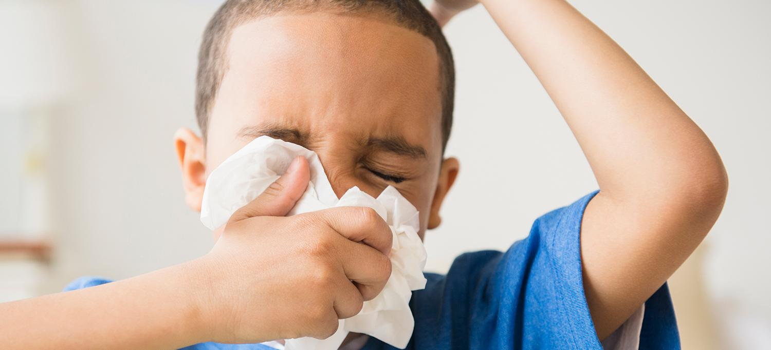 Child Sneezes into Tissue