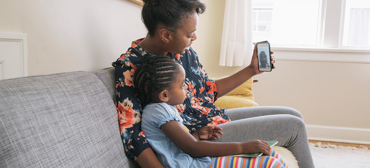 Mother and Daughter Use Mobile Phone to Video Chat