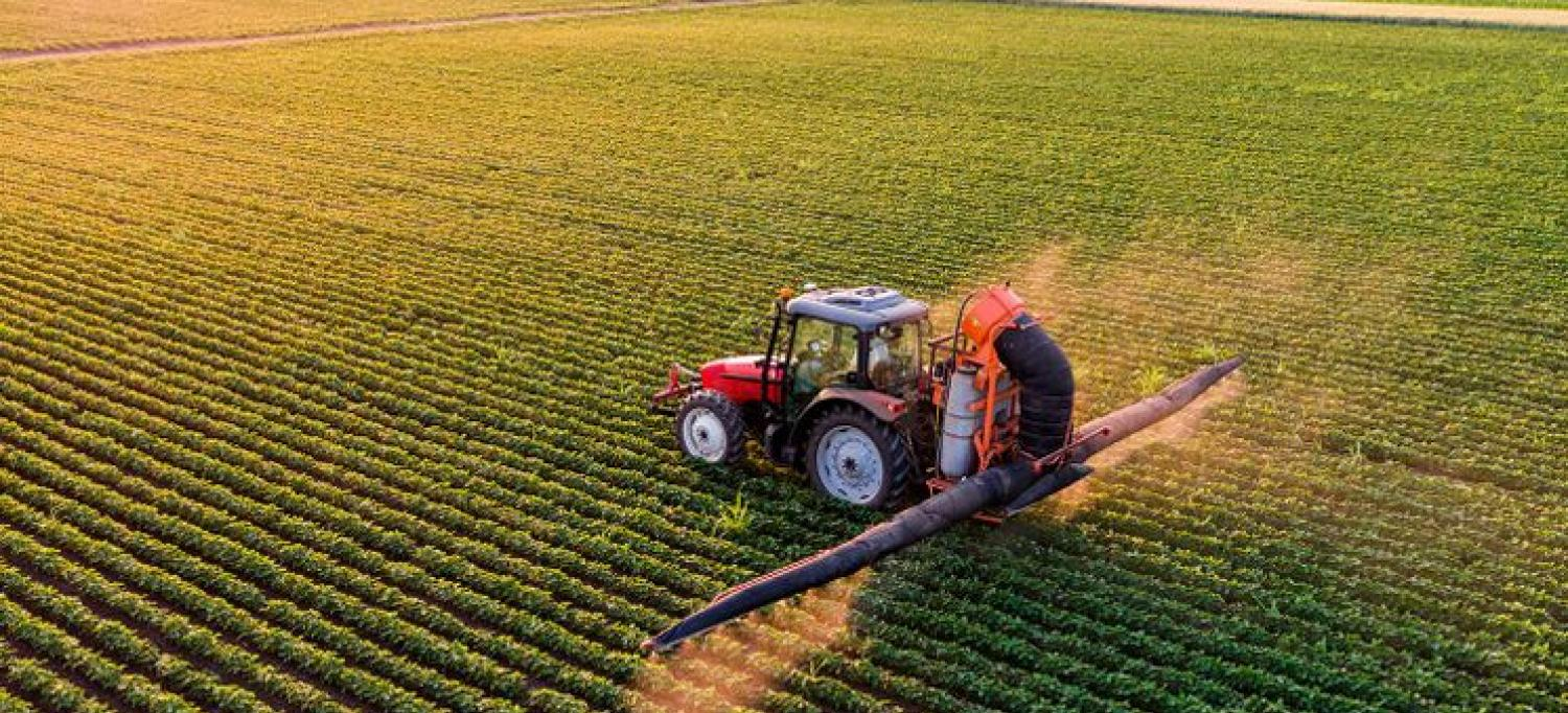 Tractor Sprays Pesticides on Crops