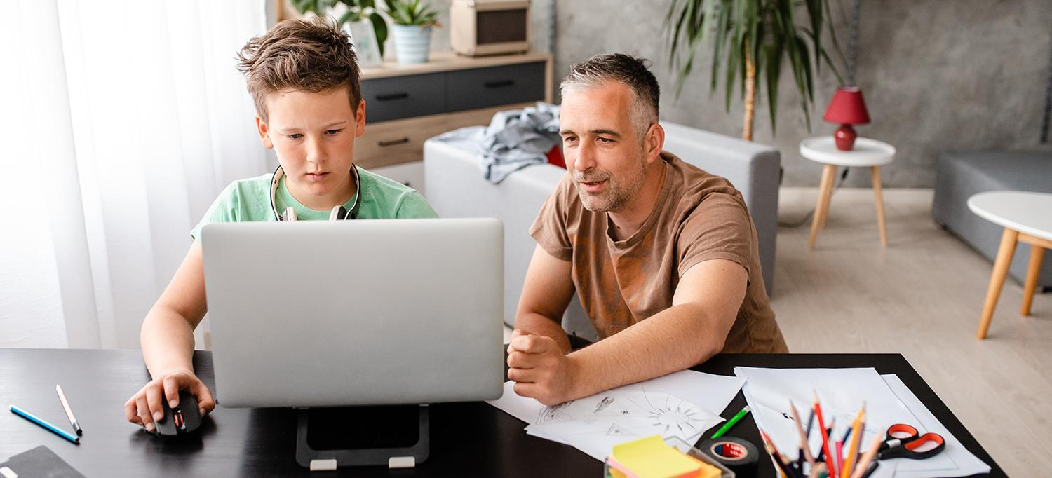 Father Helps Son with Schoolwork on Laptop Computer