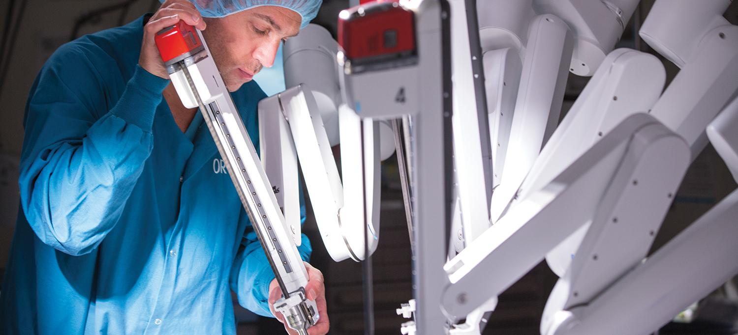 Doctor Positions a Robotic Surgery Machine in Preparation for Surgery