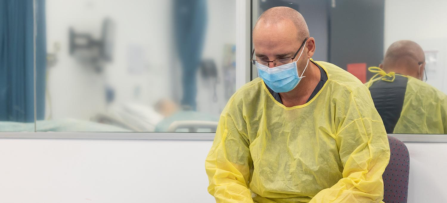 Healthcare Provider in Personal Protective Equipment Hunched Over in Chair