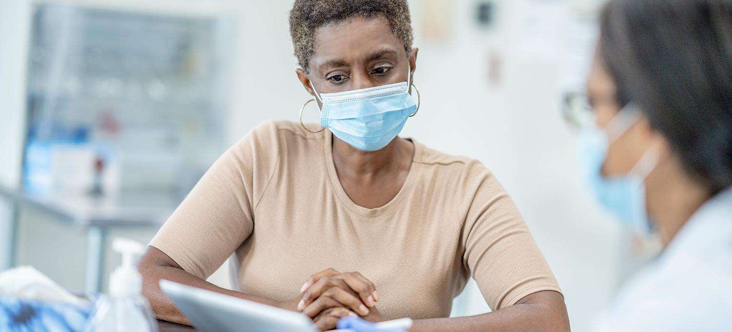 Woman Wearing Mask Speaks with Healthcare Provider Wearing Mask