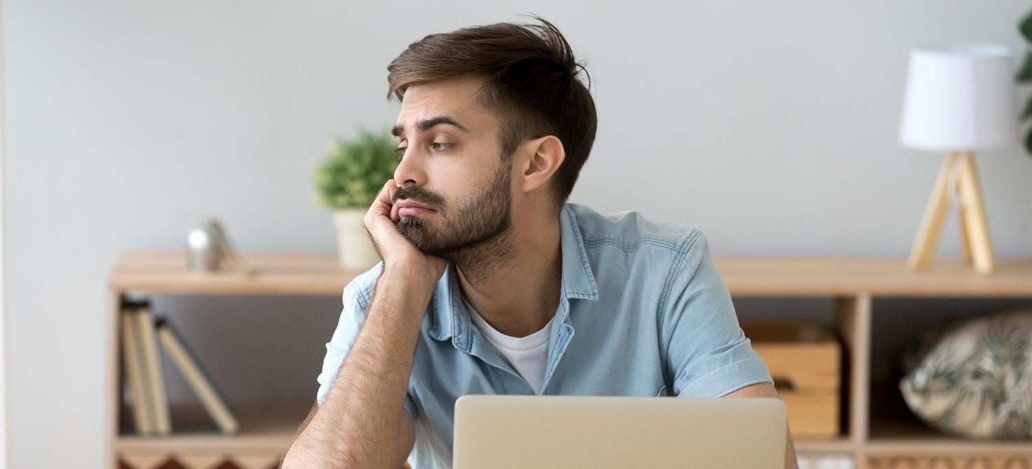 Man Sitting at Desk, Staring Off to the Side