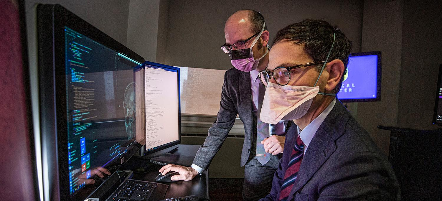 Dr. Eric K. Oermann and Dr. Daniel A. Orringer Wearing Face Masks and Reviewing Computer Analyses